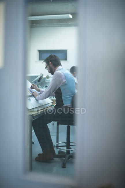 Executive working over drafting table in modern office — Stock Photo