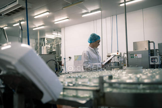 Female worker monitoring the glass jars on the production line in the factory — Stock Photo
