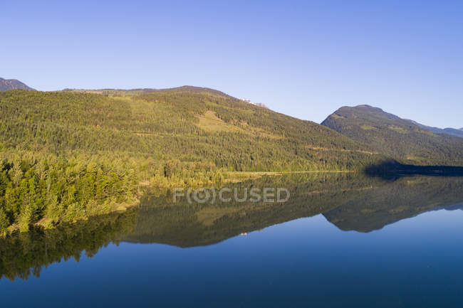 Scenic view of green mountains along the river coast — Stock Photo