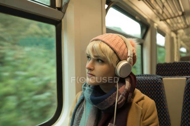 Close-up de jovem na listagem de roupas quentes para música em fones de ouvido — Fotografia de Stock