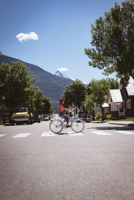 Девушка Велосипед езда на зебру в Солнечный город. — стоковое фото