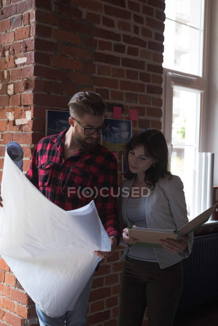 Male and female executives discussing over blueprint in office — Stock Photo