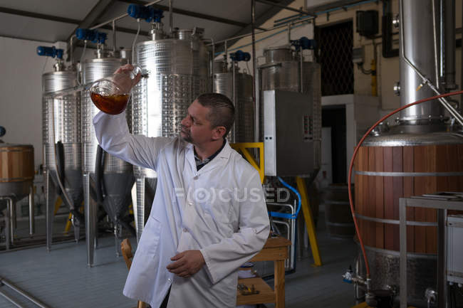 Male worker checking quality of gin in factory — Stock Photo