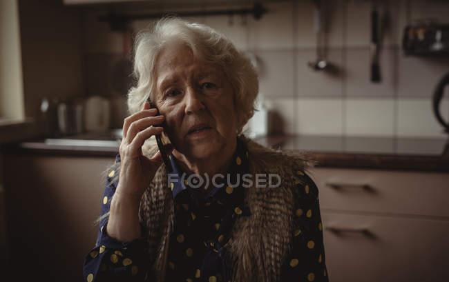 Femme âgée inquiète parlant au téléphone dans la cuisine à la maison — Photo de stock