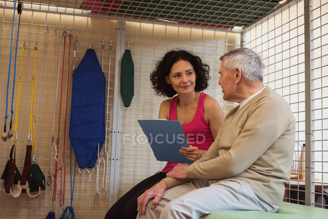 Female therapist discussing with senior man at nursing home — Stock Photo