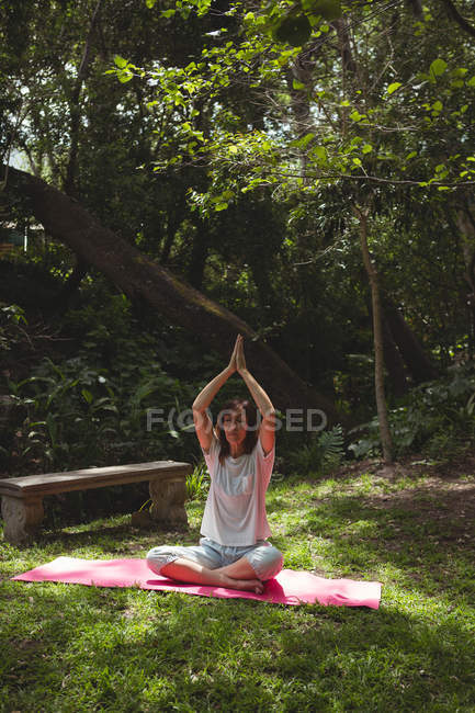 Woman practicing yoga in garden on a sunny day — Stock Photo