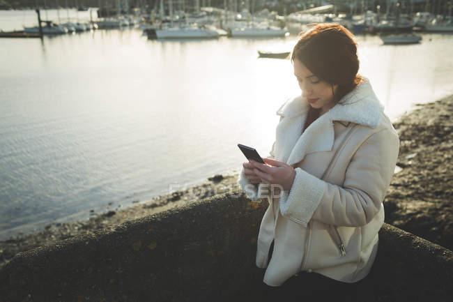 Donna che utilizza il telefono cellulare vicino al fiume dall'acqua . — Foto stock