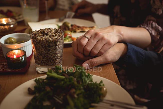 Coppia che si tiene per mano mentre pranza a tavola — Foto stock