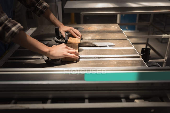 Mid section of female artisan measuring wooden piece in workshop. — Stock Photo