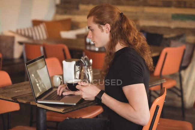 Человек, используя ноутбук имея кофе в кафе — стоковое фото