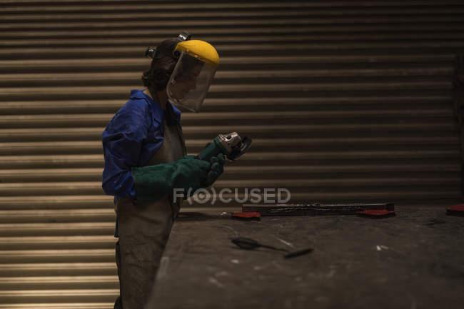 Жіночий зварювальник, тримаючи факел зварювання в майстерні. — Stock Photo