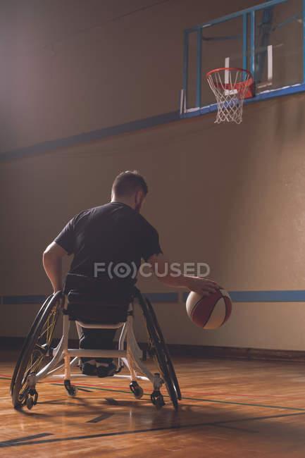 Вид сзади на инвалида, практикующего баскетбол на площадке — стоковое фото