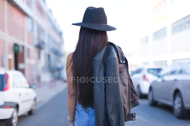 Vista trasera de la adolescente posando en la calle de la ciudad - foto de stock
