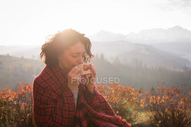 Alpinista feminina em cobertor ter café em um dia ensolarado — Fotografia de Stock