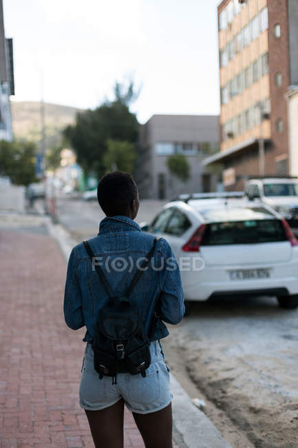 Rear view of woman standing on a sidewalk in city street — Stock Photo