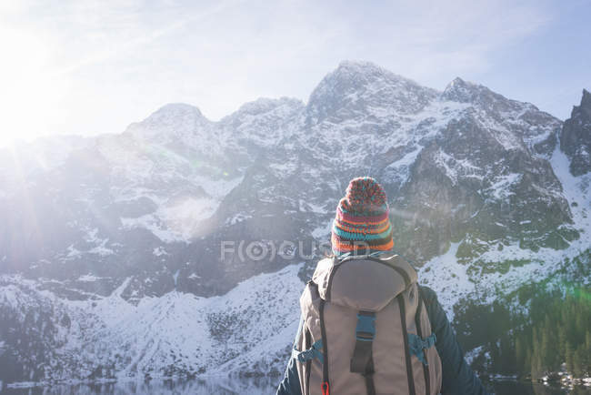 Rear view of female hiker looking at snow capped mountain — Stock Photo