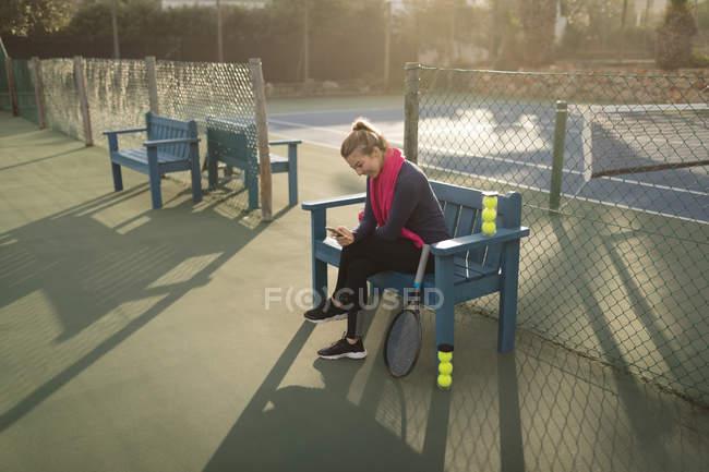 Молода жінка, що використання мобільного телефону у тенісний корт — стокове фото
