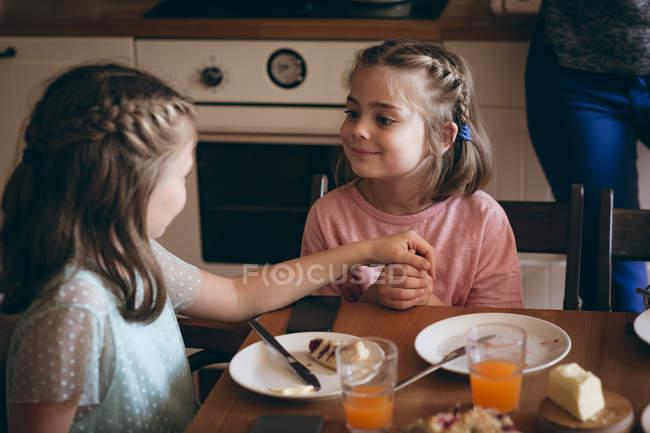 Schwestern, die Interaktion mit einander beim Frühstück in der Küche — Stockfoto