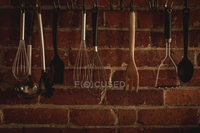 Various kitchenware against hanging brick wall — Stock Photo