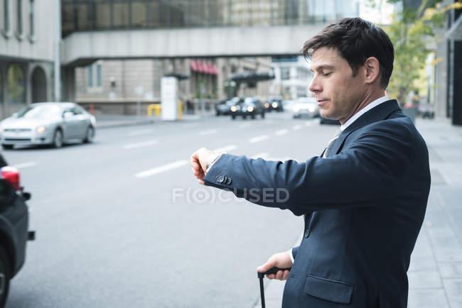 Бизнесмен, проверка времени на наручные часы на улице — стоковое фото