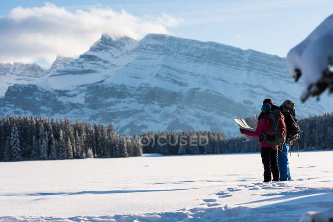 Couple of backpackers looking at map in snowy landscape during winter. — Stock Photo
