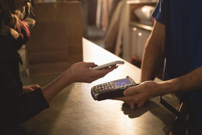 Девушка делает оплату через мобильный телефон на прилавке — стоковое фото