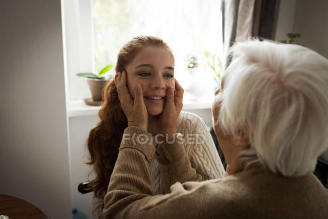 Бабушка трогательно внучка лицо дома — стоковое фото
