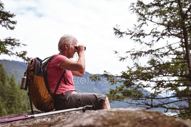 Vista laterale della donna matura seduta sulla roccia guardando attraverso il binocolo — Foto stock