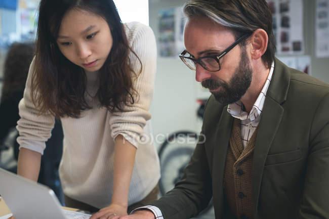 Dirigeants discutant sur ordinateur portable dans le bureau moderne — Photo de stock