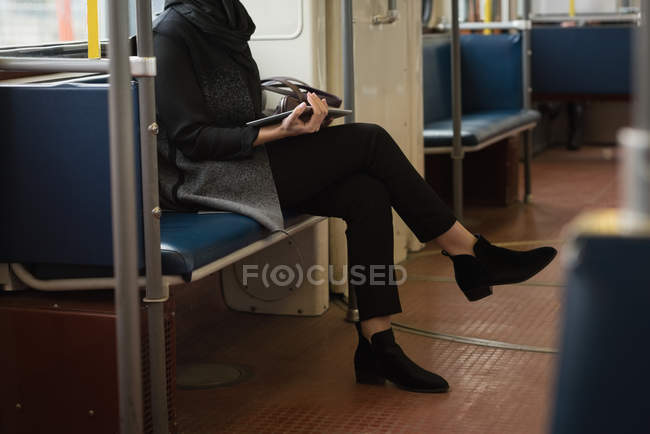 Женщина с ногами перешли с использованием цифровых таблетки во время поездки в поезде — стоковое фото