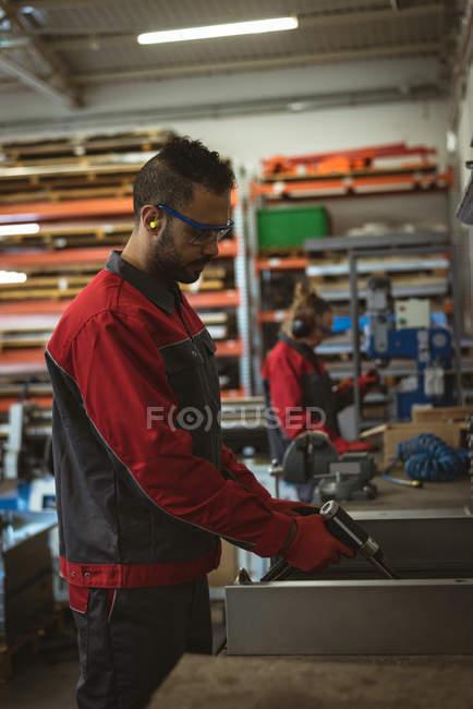 Работник-мужчина ремонтирует станок с помощью инструмента на заводе — стоковое фото