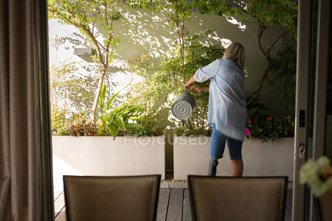 Rear view of woman with prosthetic leg watering plants in porch at home. — Stock Photo