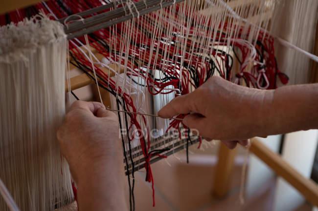 Close-up of senior woman weaving silk at shop — Stock Photo