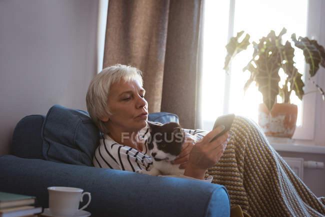 Старшая женщина сидит на диване со своей кошкой во время использования мобильного телефона в гостиной на дому — стоковое фото