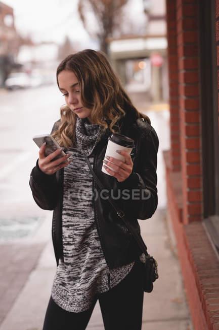 Belle jeune fille à l'aide de mobile tout en buvant le café à l'extérieur du centre commercial — Photo de stock