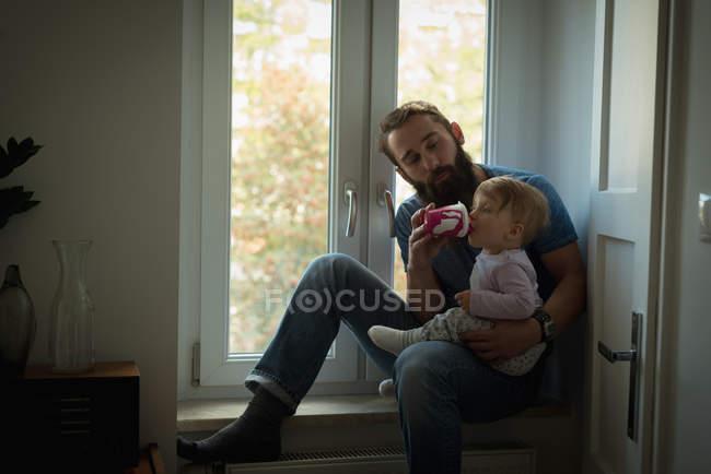 Padre alimentando a su hijo en casa - foto de stock