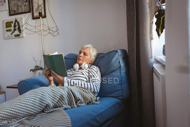 Femme âgée se détendant sur un canapé lisant un livre dans le salon à la maison — Photo de stock