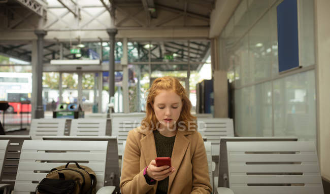 Front view of young woman using her mobile phone at bus stop — Stock Photo