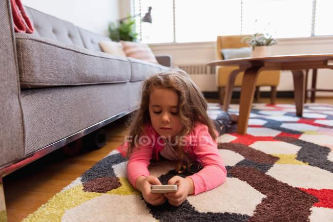 Ragazza che si trova sul tappeto e utilizzando il telefono cellulare in salotto a casa — Foto stock