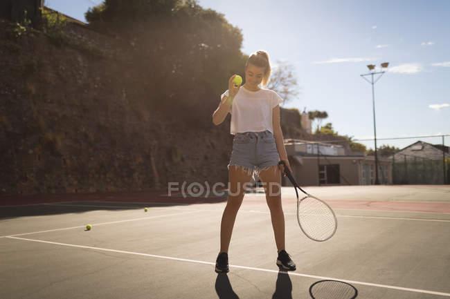 Mulher praticando tênis no campo de tênis em um dia ensolarado — Fotografia de Stock