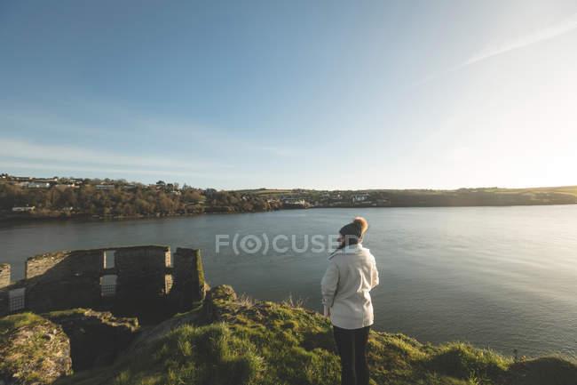 Vista posteriore della donna in piedi vicino al lungofiume durante il tramonto . — Foto stock