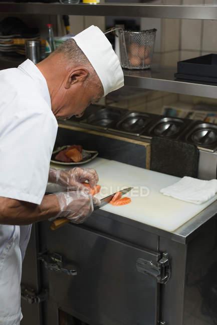 Шеф-повар готовит суши в ресторане кухня — стоковое фото