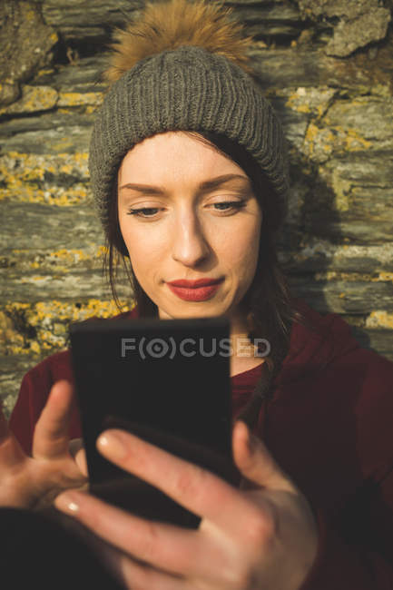 Woman using mobile phone against wall in sunlight. — Stock Photo
