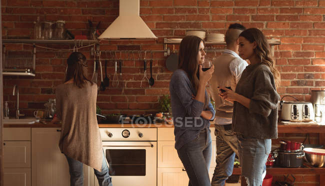 Friends having wine while preparing food in kitchen — Stock Photo
