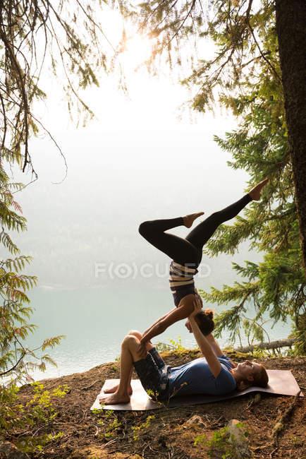 Sportliches Paar praktiziert an einem sonnigen Tag Acroyoga in Küstennähe — Stockfoto