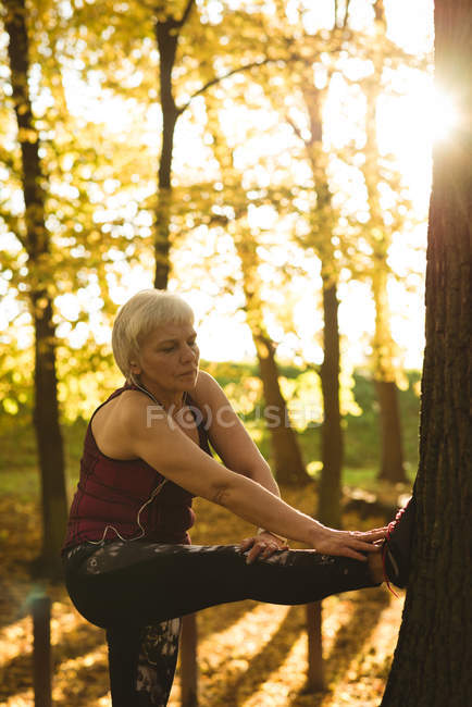 Senior woman performing stretching exercise in the park on a sunny day — Stock Photo