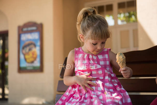 Girl looking at droplets of melted ice cream falling on dress — Stock Photo