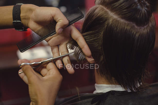 Man getting his hair trimmed with scissor at barbershop — Stock Photo