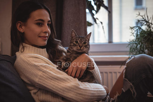 Улыбающаяся женщина сидит дома со своим домашним котом — стоковое фото