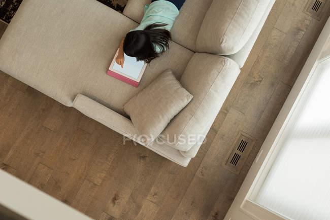Вид сверху на девушку с помощью цифрового планшета в гостиной на дому — стоковое фото